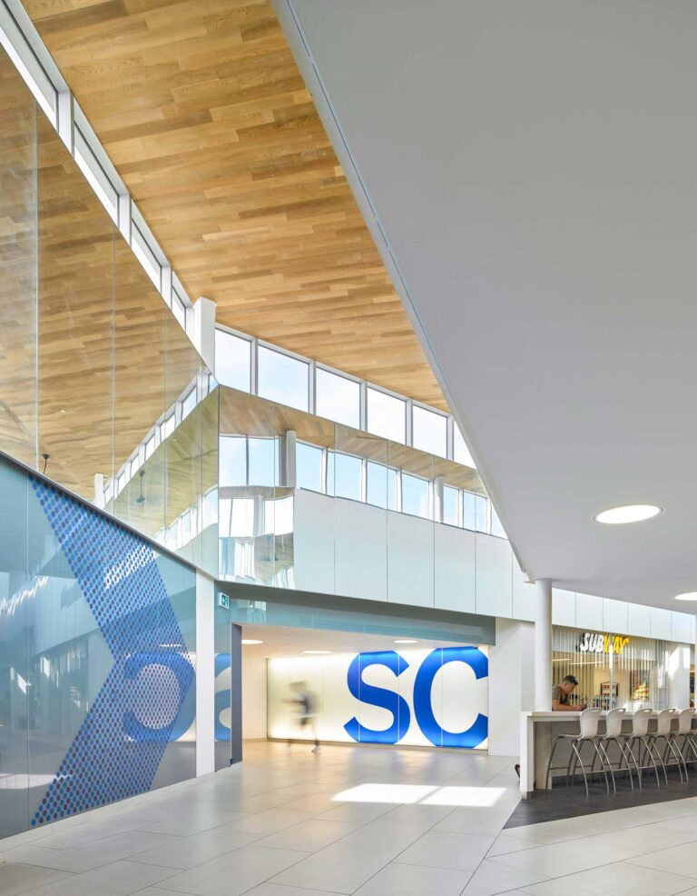 A wood soffit ceiling with clerestory windows guides students through the Student Commons at Niagara College.