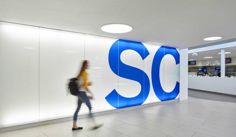 A student walks by a brand graphic of a cobalt blue SC on a white wall.