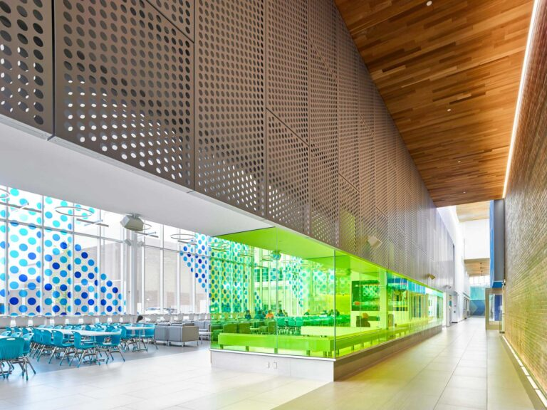 Glass in an internal corridor is lined with a colourful film to introduce a pop of colour.