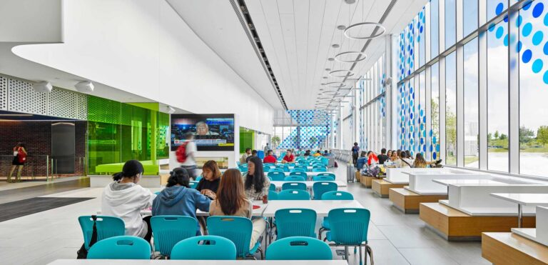 Students gather in the daylit space next to a wall of windows.
