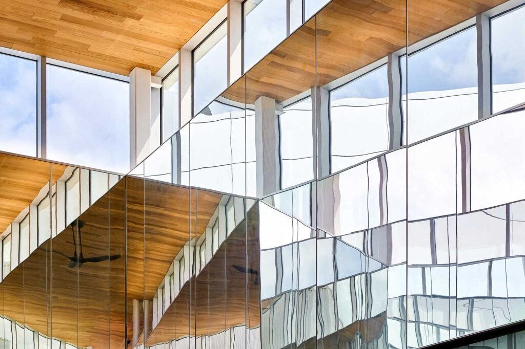 Light and sky views are refracted in the mirrors underneath the wood lined cedar ceiling at Niagara College Student Commins.