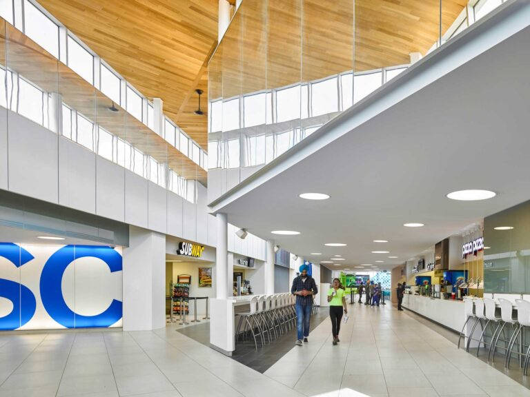 Two students walk through the student centre underneath the wood clad soffit ceiling.