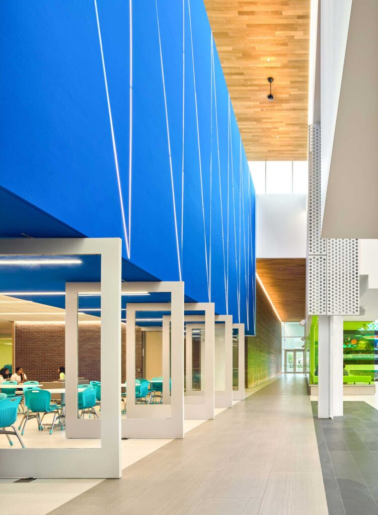 A bright blue feature wall above pivoting white doors at the Niagara College Student Commons.